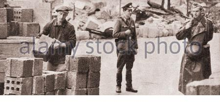 Start of the construction of the Berlin Wall. East German workers unload and cement concrete blocks to build the Berlin Wall under armed guards. Berli Stock Photo