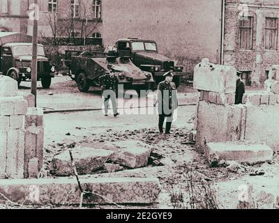 Construction of the Berlin Wall. Gap in the wall. Communist border guards inspect a gap in the Berlin wall where two East German construction workers Stock Photo