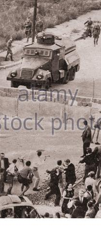 Start of the construction of the Berlin Wall. At a demonstration, West Berliners protest against the recently constructed Berlin Wall throw rocks over - Stock Photo