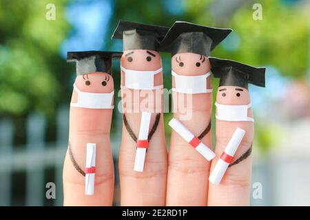 Fingers art of students in medical mask from COVID-2019. Graduates holding their diploma after graduation.