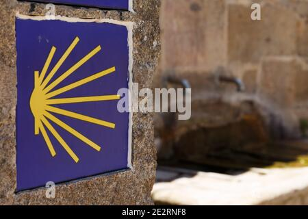 St.James way, yellow scallop sign with a fountain on the background, Finisterre, Galicia, Spain