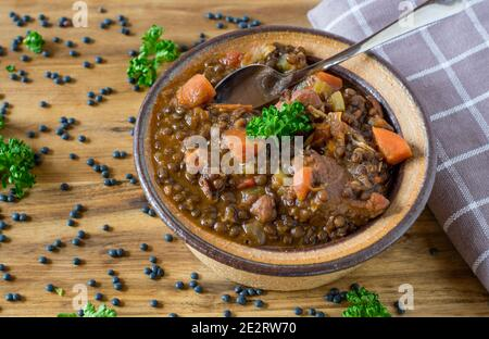 lentil soup with meat  in a bowl  on wooden background from above - Stock Photo