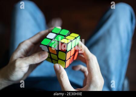 Bangkok, Thailand - January 13, 2021 : A man solving Rubik's cube.