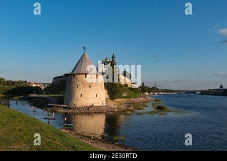 SUP surfers on Velikaya river. Towers and wall of Pskov Kremlin at background. Pskov, Russia.