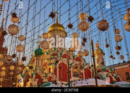Russia, Moscow, December 2020. View of the Kazan Church from Nikolskaya Street through festive garlands.