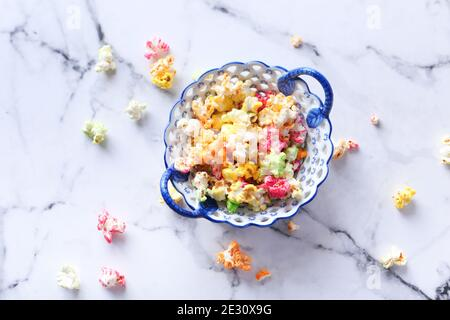 colorful popcorn in a bowl on tiles background top down