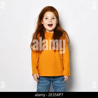 Excited surprised red-haired kid girl in orange sweatshirt and blue jeans stands with opened mouth