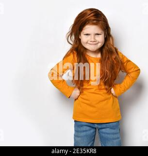 Frolic red-haired kid girl in orange sweatshirt and blue jeans stands with fists at waist playing displeased strict mom