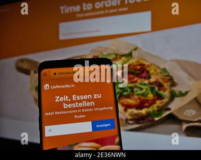 Website of online food delivery company Lieferando.de displayed on smartphone. Text: Time to order food. Find restaurants in your area.