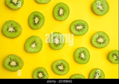 Fresh kiwi slices isolated on yellow background