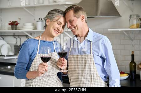 Happy old couple bonding, drinking wine standing in kitchen cooking at home.