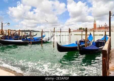 Gondolas along the Grand Canal with the Riva di Schiavoni and the Church and island of San Giorgio Maggiore visible in the distance in Venice, Italy.