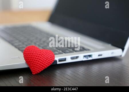 Valentine heart on a desk near the laptop. Red knitted symbol of love, gift for holiday Stock Photo