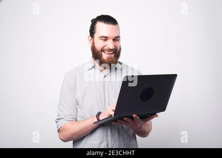 Portrait of happy bearded man in shirt using laptop over white wall.