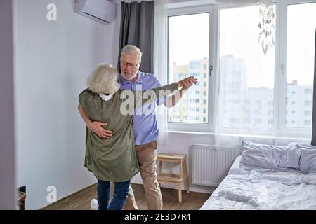 senior couple have fun dancing at home, romantic mature grey-haired man and woman feel energetic active enjoy family retirement weekend, spend holiday