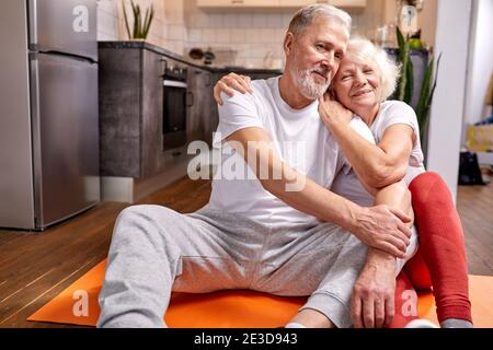 senior couple having rest on the floor after yoga exercises, in sportive wear, look at camera and smile