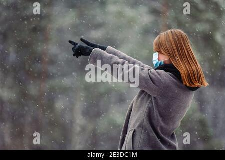 Young caucasian girl in a medical mask looks away and points with both hands with index fingers to the side against the background of the forest and