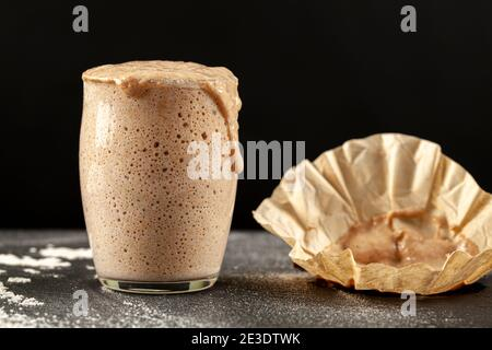Side view of an actively rising sourdough starter culture which is overflowing over the top of the glass cup it is in. Bubbles show fermentation. The
