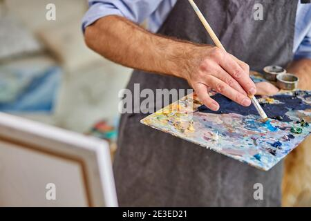artist mix colors on palette holding in hand close up. creativity, art concept