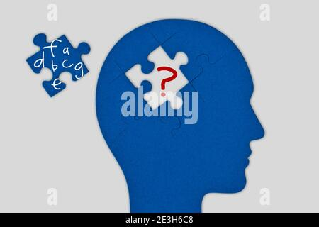 Head profile with brain made of jigsaw puzzle pieces on white background - Concept of dyslexia and problems with words