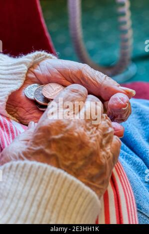 An elderly lady carefully counting money with coins in her hands. - Stock Photo