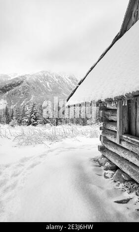 Black and white picture of wooden hut at Gasienicowa Valley (Hala Gasienicowa) during snowy winter, Tatra Mountains, Poland. - Stock Photo
