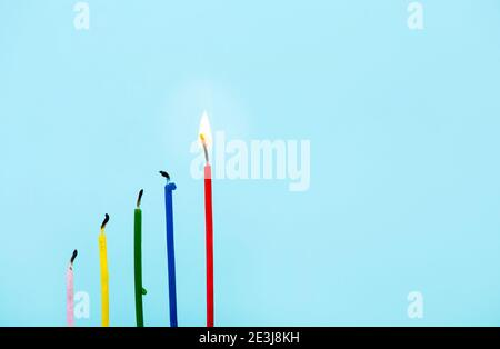 Group of candles burned out and one red tall burning on light blue background. Idea, success concept. Lot of copy space.