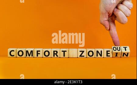 Out or in comfort zone symbol. Hand turns wooden cubes and changes words 'in comfort zone' to 'out comfort zone'. Beautiful orange background, copy sp