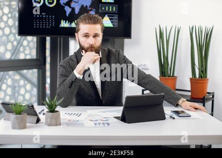 Handsome purposeful confident bearded businessman, chief executive officer in formal wear, sitting at workplace and looking at camera. Male worker
