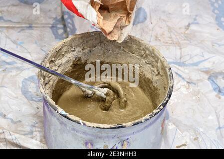 kneading cement mortar in saucepan. preparation for repair - Stock Photo