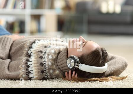 Relaxed teen listening to music wearing headphones lying at home in winter