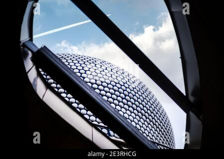 Birmingham UK December 2020 Bullring shopping centre looking up to the sky with clouds and aeroplane flying over modern architecture with silver discs