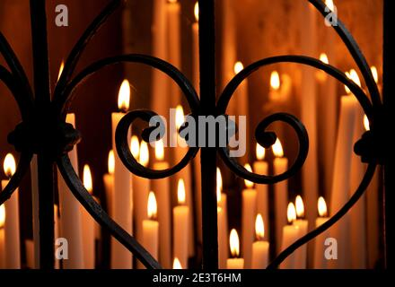 Golden candles light in dark temple seen through forging fence in heart shape. Religious background. Selective focus on the fence. Blurry lights.