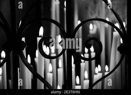 Candles light in dark temple seen through forging fence in heart shape. Religious background. Selective focus on the fence. Blurry lights. Black and w