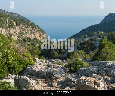 A view of valley with rocky hiking path to Cala Goloritze beach, limestone rocks and sea. Famous travel destination. Gulf of Orosei, Sardinia, Italy