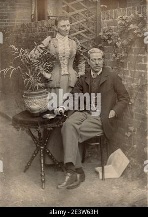 Affectionate home photo of 1890s Victorian unknown fashionably dressed mature man and transgender cross dressed partner in a garden. One of a sequence of ten photographs of friends and family in the same setting.