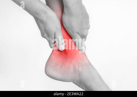 Woman with ankle pain holding her aching leg - black and white photo Stock Photo