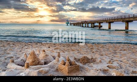 Pier and beach with sand castles in foreground in Zinnowitz at sunset. Baltic Sea, island Usedom, Germany