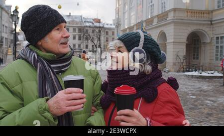 Senior wife and husband tourists drinking from cups, enjoying hot drink tea, coffee on winter city central street in Lviv, Ukraine. Family man and woman vacation trip activities. Life after retirement
