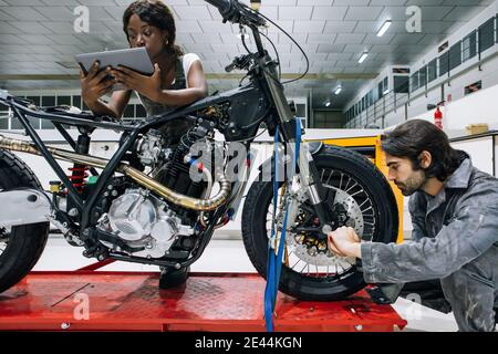 Black female mechanic using tablet and male technician repairing wheel of motorbike with screwdriver while working in spacious workshop together