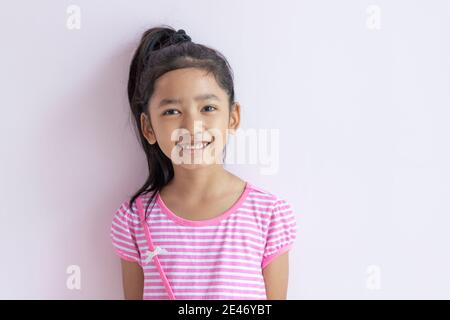 Portrait of an Asian little girl wearing a pink and white striped dress. The child tied up black hair and smiled with happiness. - Stock Photo