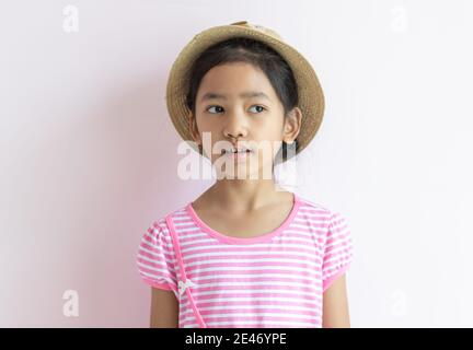 Portrait of an Asian kid wearing a pink and white striped dress. The girl wore a hat and looking to her side. - Stock Photo