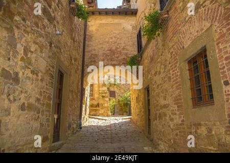 A stone archway across a quiet residential street in the historic medieval village of Montefioralle near Greve in Chianti in Florence province, Tuscan