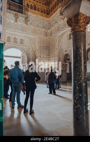 Seville, Spain - January 19, 2020: Tour group inside Hall of Ambassadors in Alcazar of Seville, a royal palace built for the Christian King Peter of C - Stock Photo