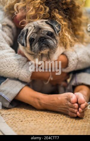 Love and friendship concept with people and animals - happy woman hug her old nice pug at home on the floor - pet therapy healthy lifestyle concept