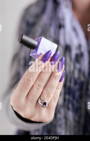 Female hand with purple long nails and nail polish bottle