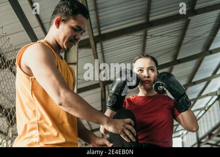 woman wearing boxing gloves with her trainer standing on the boxing ring