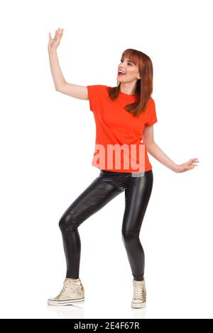 Young woman in orange t-shirt, black leather pants and gold sneakers is dancing, looking away and shouting. Full length studio shot isolated on white.
