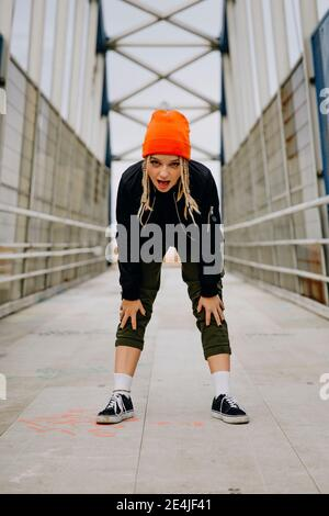 Young woman with mouth open bending while standing on footbridge