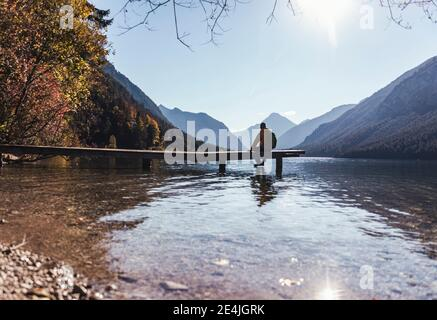 Silhouette male hiker sitting on pier over lake against sky during sunny day - Stock Photo
